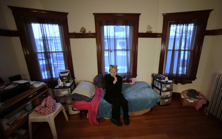 In this Friday, Feb. 20, 2015 photograph, Charla Nash, who is blind, rests in her bedroom between her speakerphone and boom box at her second-story apartment in Boston. Nash, who lost her face, eyes and hands after being mauled by a chimpanzee in 2009, spends much of her time listening to the radio and books on tape. The military is hoping the information they learn from Nash's face transplant rehabilitation can help young, seriously disfigured soldiers returning from war. (AP Photo/Charles Krupa)
