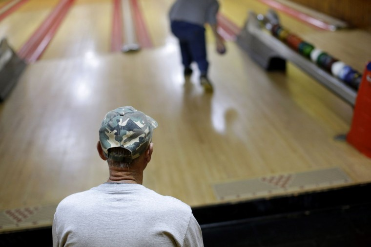Jerry Middleton watches as his son Jon hurls a duckpin bowling ball during a tournament at Shenandoah Bowling Lanes, Saturday, March 28, 2015, in Mount Jackson, Va. The sport, which is mostly played in the Mid-Atlantic, enjoyed its peak in the 1960s. (AP Photo/Patrick Semansky)