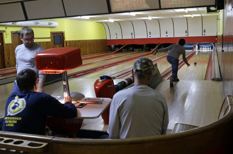 George Daugharty, right, watches his duckpin bowling ball roll down a lane during a tournament at Shenandoah Bowling Lanes, Saturday, March 28, 2015, in Mount Jackson, Va. Duckpin bowling is a variation of the more popular 10-pin bowling, with smaller pins and a ball slightly larger than a softball. (AP Photo/Patrick Semansky)