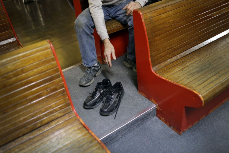 Jerry Middleton reaches for his duckpin bowling shoes after a tournament at Shenandoah Bowling Lanes, Saturday, March 28, 2015, in Mount Jackson, Va. Shenandoah, open since 1948, is one of around 60 remaining duckpin alleys in the United States. (AP Photo/Patrick Semansky)