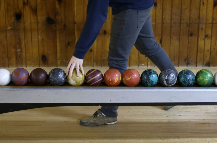 Scott Asbell reaches for a duckpin bowling ball during a tournament at Shenandoah Bowling Lanes, Saturday, March 28, 2015, in Mount Jackson, Va. The sport, which is mostly played in the Mid-Atlantic, enjoyed its peak in the 1960s. (AP Photo/Patrick Semansky)