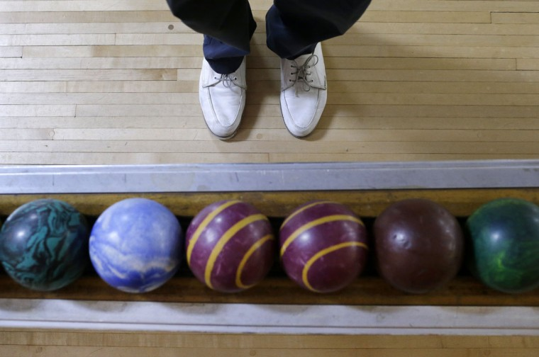 Josh Miller stands next to a rack of duckpin bowling balls during a tournament at Shenandoah Bowling Lanes, Saturday, March 28, 2015, in Mount Jackson, Va. The sport, which is mostly played in the Mid-Atlantic, enjoyed its peak in the 1960s. Shenandoah, open since 1948, is one of around 60 remaining duckpin alleys in the United States. (AP Photo/Patrick Semansky)