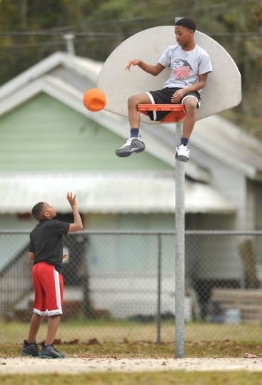 With the temperature in the high 70's, (left) Kevin Hamilton, 12 and his friend Leroy Whitaker, 14 enjoy the warm spring like day as they play on the basketball courts at Central Riverside Elementary School in Jacksonville, Fla., Sunday, Feb. 22, 2015. (AP Photo/The Florida Times-Union/Bob Self)