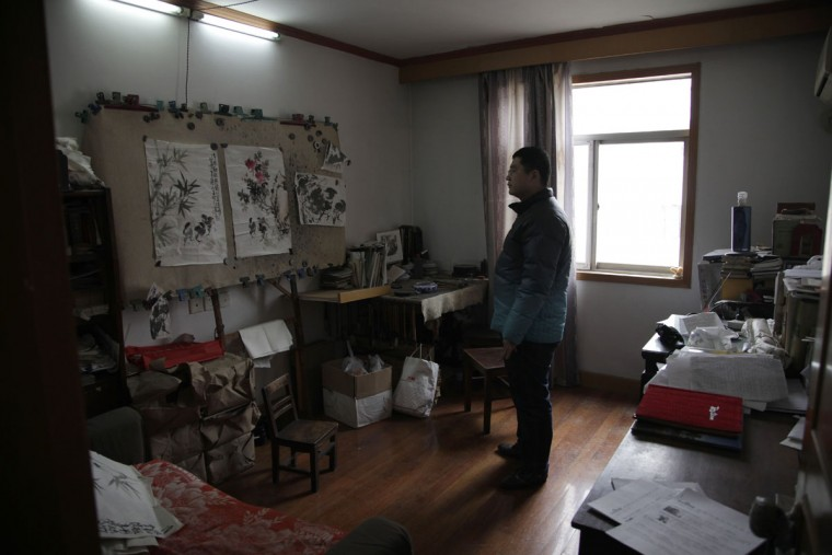 Wang Zheng looks at the work room of his father Wang Linshi who was onboard the missing Malaysia Airlines Flight 370, at an apartment in Nanjing in eastern China's Jiangsu province. For the past year, Wang Zheng has been avoiding one place: the modest apartment where his parents had been living for more 20 years until they vanished along with the ill-fated flight. Scrolls of paintings by his father are in piles in the living room, the guest bedroom, and the studio. Paintbrushes - their heads long dry - hang from a workstation in a row. In the kitchen, the floor and stove have collected a thin layer of dust. Wang Zheng, the only son of Wang Linshi and Xiong Deming, said he only comes into the apartment in this eastern Chinese city when absolutely necessary. (AP Photo/Peng Peng)