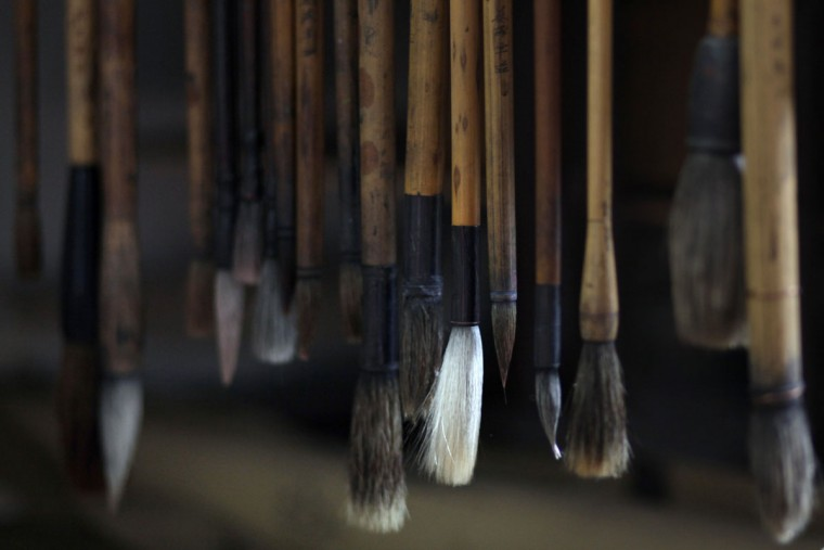 Ink brushes belonging to Wang Linshi, a Chinese artist who was onboard the missing Malaysia Airlines Flight 370, hang disused at an apartment in Nanjing in eastern China's Jiangsu province. Scrolls of paintings by Wang are in piles in the living room, the guest bedroom, and the studio. Paintbrushes - their heads long dry - hang from a workstation in a row. In the kitchen, the floor and stove have collected a thin layer of dust. (AP Photo/Peng Peng)