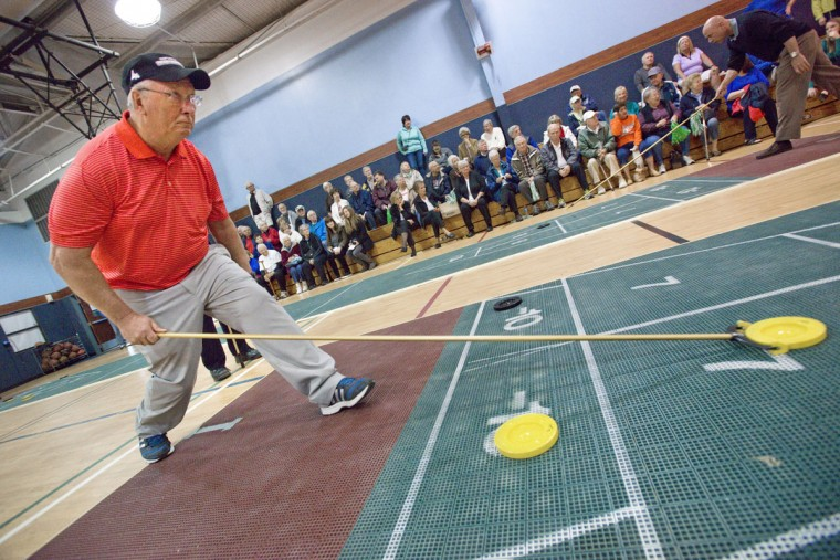 Derm Flynn, of Panama City Beach, sizes up a shot during the annual Snowbird Shuffleboard Tournament, Wednesday, Feb. 25, 2015, at the Destin Community Center in Destin, Fla. (AP Photo/Northwest Florida Daily News, Devon Ravine)