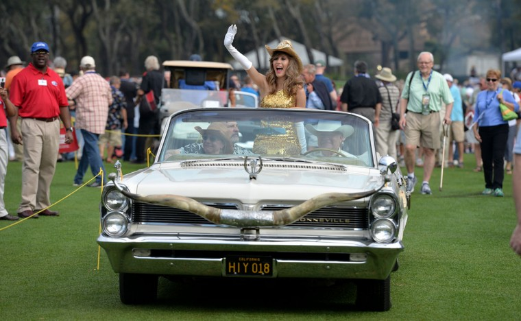 "Christina Garza rides down the fairway in the 1963 Pontiac Bonneville designed by Nudie Cohn the ""Rodeo Tailor to the Stars"" during the fashion show Sunday, March 15, 2015 in Amelia Island, Fla. The 20th Amelia Island Concours d'Elegance, was held at the on the golf club of the Ritz-Carlton. Sir Sterling Moss, 85, legendary British race car driver, was this year's honoree. (AP Photo/Florida Times-Union, Bruce Lipsky)"
