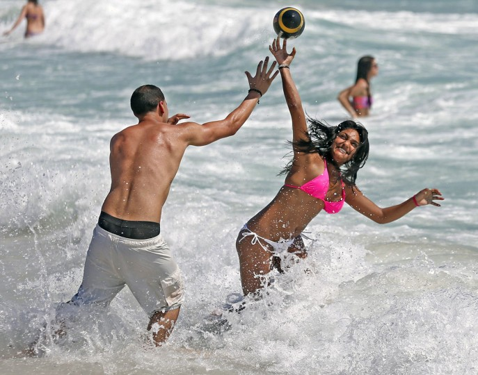 Mike Sierra, 21, and Larissa Macko, 21, spring breakers from the University of Central Florida, play ball on South Beach on Tuesday, March 10, 2015 in Miami Beach, Fla. (AP Photo/The Miami Herald, Al Diaz)