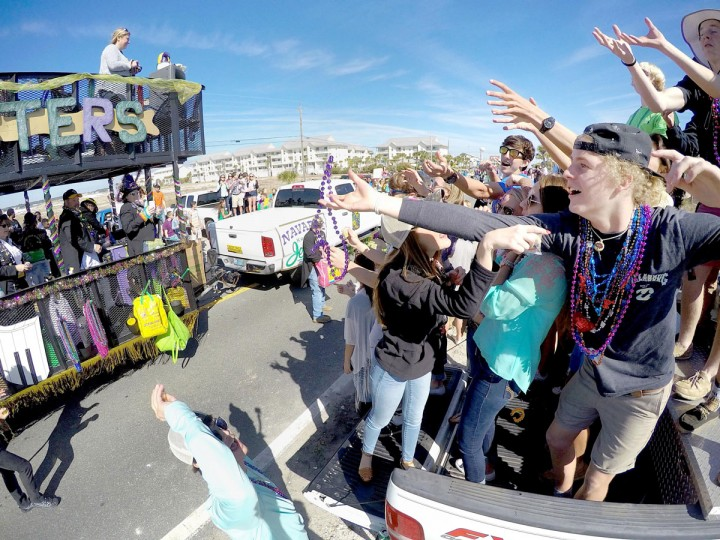 Parade revelers beg for beads while standing in the bed of a pick-up truck on Navarre Beach for the annual Navarre Beach Mardis Gras Parade in Navarre, Fla., on Feb. 7, 2015. (AP Photo/ Northwest Florida Daily News, Nick Tomecek)