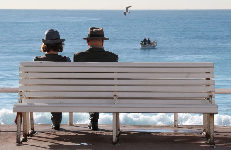 People sit on a bench on the promenade des Anglais in Nice, southeastern France, Wednesday, Feb. 25, 2015. Temperatures in the area rose to 16 degrees Celsius (60 Fahrenheit). (AP Photo/Lionel Cironneau)