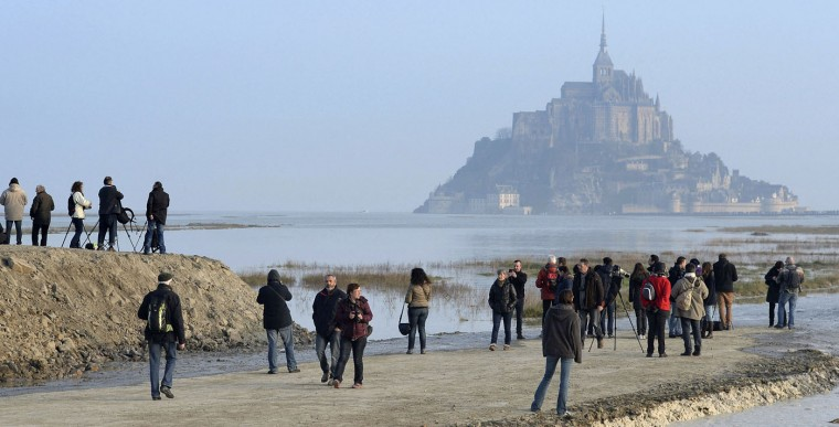 """People gather to watch the water surround Mont Saint-Michel on France's northern coast. A supertide has turned France's famed Mont Saint-Michel into an island and then retreated out of sight, delighting thousands of visitors who came to see the rare phenomenon The so-called """"tide of the century"""" actually happens every 18 years. (Associated Press)"""