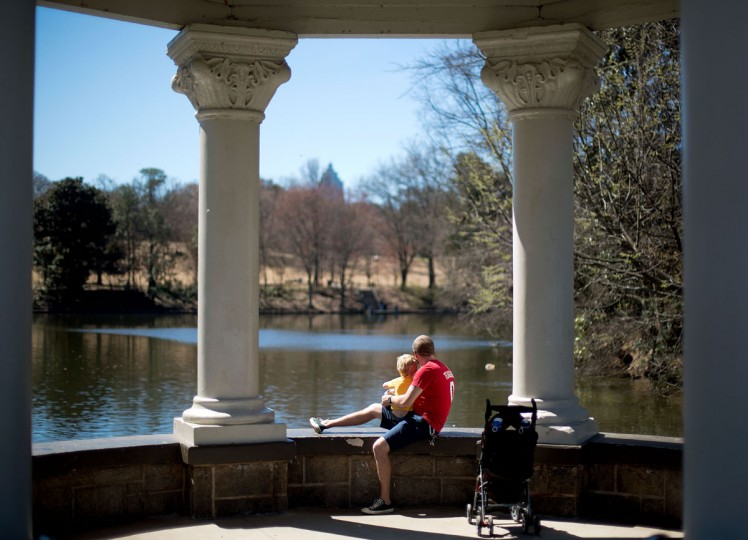 Keith Johnson, right, sits with his son Tommy, 2, both of Lilburn, Ga., while watching ducks swim by in Piedmont Park, Monday, March 16, 2015, in Atlanta. Temperatures are expected to reach near 80 degrees Monday in the metro Atlanta area. (AP Photo/David Goldman)