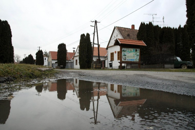 "In this Wednesday, Feb. 25, 2015 file photo, houses are reflected in a puddle on the main road in the village of Megyer, Veszprem county, 190 kilometers (120 miles) southwest of Budapest, Hungary. Rooms at Hungaryís village-for-rent are going fast. Over 300 inquiries and reservations for 280 guests have been made since Mayor Kristof Pajer last week began advertising the village of Megyer, available for 210,000 forints ($760; 690 euros) a day. Pajer said Thursday, March 5, 2015, tourists are coming from as far away as Australia, South Africa, Sweden and the United States and the village ""is booked solid in August and most of April and May."" (AP Photo/MTI, Lajos Nagy, File)"