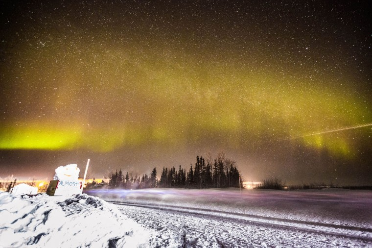 In this Friday, March 13, 2015, Jason Mackey arrives in Huslia, Alaska, under the northern lights in the Iditarod Trail Sled Dog Race. (AP Photo/Alaska Dispatch News, Loren Holmes)