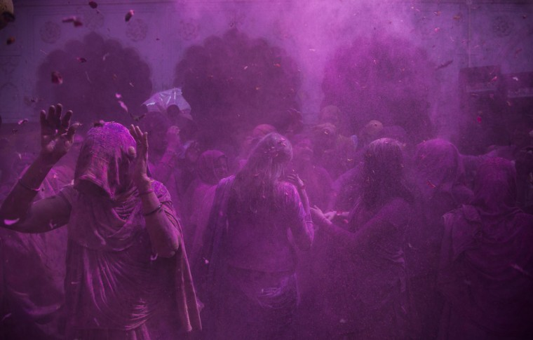 Indian Hindu widows play with colored powder as part of Holi celebrations at the Pagal Baba Ashram in Vrindavan, India, Tuesday, March 3, 2015. The widows, many of whom at times have lived desperate lives in the streets of the temple town, celebrated the Hindu festival of colors at the ashram. (AP Photo/Tsering Topgyal)