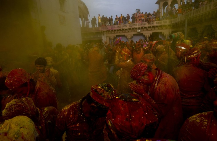 Indian Hindu devotees pray as others throw colored powder on them at the Nandagram temple, famous for Lord Krishna and his brother Balram, during Lathmar holi festival, in Nandgaon, India, Saturday, Feb. 28, 2015. During Lathmar Holi the women of Nandgaon, the hometown of Krishna, beat the men from Barsana, the legendary hometown of Radha, consort of Hindu God Krishna, with wooden sticks in response to their teasing as they depart the town. (AP Photo/Saurabh Das)