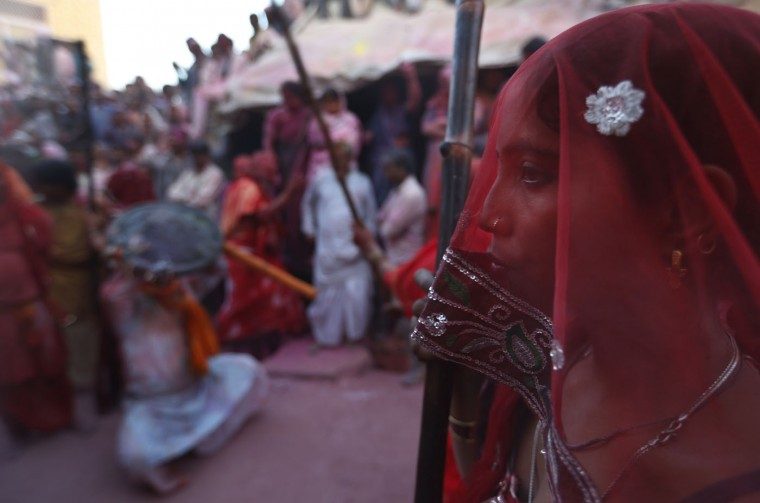 A Hindu woman is seen through her veil as other women beat men from Nandgaon village during Lathmar Holi festival, at the legendary hometown of Radha, consort of Hindu God Krishna in Barsana, 115 kilometers (71 miles) from New Delhi, India, Friday, Feb. 27, 2015. During Lathmar Holi the women of Barsana beat the men from Nandgaon, the hometown of Lord Krishna, with wooden sticks in response to their teasing. (AP Photo/Saurabh Das)