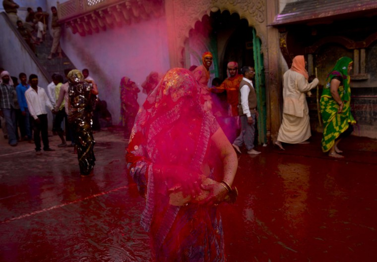 Colored powder is thrown on a woman devotee during Lathmar holi festival celebrations, in Nandgaon, India, Saturday, Feb. 28, 2015. During Lathmar Holi the women of Nandgaon, the hometown of Krishna, beat the men from Barsana, the legendary hometown of Radha, consort of Hindu God Krishna, with wooden sticks in response to their teasing as they depart the town. (AP Photo/Saurabh Das)