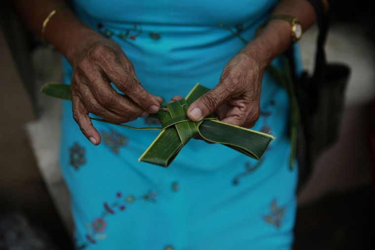An Indian Christian devotee makes a cross with palm leaves after she arrived for the Palm Sunday mass at a Church in Mumbai, India, Sunday, March 29, 2015. Christians comprise 2 percent of India's more than 1.2 billion people. (AP Photo/Rafiq Maqbool)