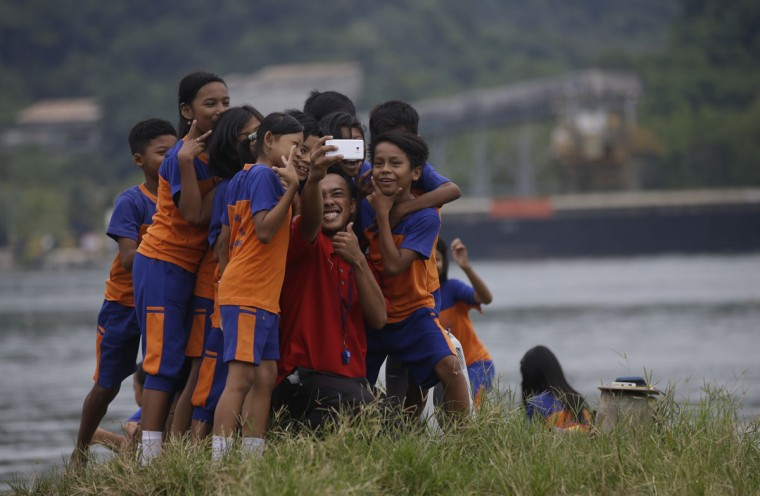 A teacher and students take a selfie at Wijaya Pura port in Cilacap, Central Java, Indonesia, Thursday, March 5, 2015. (AP Photo/Achmad Ibrahim)