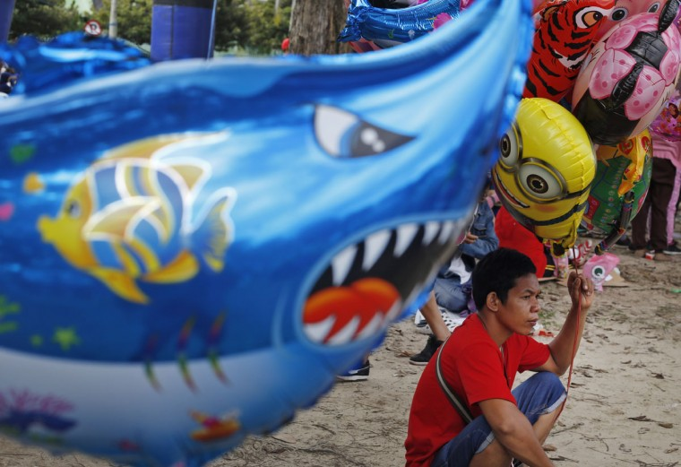 A balloon vendor waits for customers during a car free day event in Balikpapan, East Borneo, Indonesia, Sunday, March 29, 2015. (AP Photo/Dita Alangkara)
