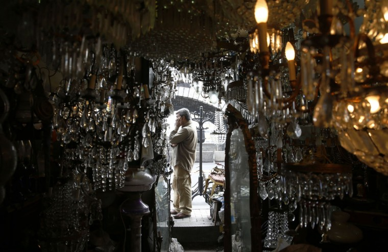 A junk dealer talks on the phone outside his shop in Catania, Italy, Wednesday, March 25, 2015. (AP Photo/Luca Bruno)