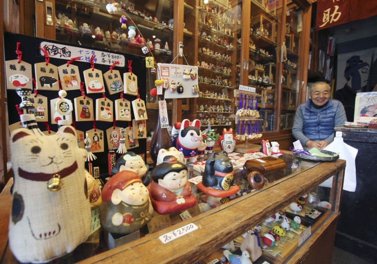Yoshitaka Kimura sits at his toy store at the Asakusa Nakamise shopping area in Tokyo. Kimura, sixth generation heir to the familyís toy business, was just seven when his family fled during the firebombing from their shop near Asakusaís famous Sensoji Temple, heading toward the Sumida River. The blast from a falling bomb blew him under the half-closed shutter of the Matsuya department store, one of the few buildings left standing after the attack. He and others crowded inside survived. (AP Photo/Koji Sasahara)