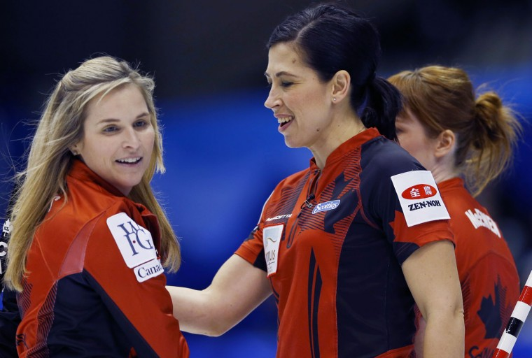 Canada's skip Jennifer Jones, left, celebrates with second Jill Officer, center, after winning against Russia during the 9th end of semi-finals during the women's World Curling Championships in Sapporo, northern Japan, Saturday, March 21, 2015. (AP Photo/Shizuo Kambayashi)