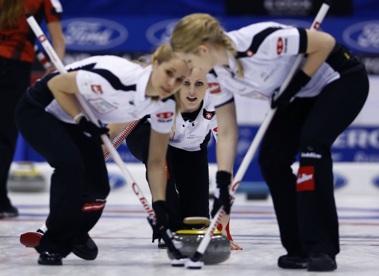 Switzerland's Nadine Lehmann, center, watches after releasing the stone in the second end during their final match against Canada at the World Women's Curling Championship in Sapporo, northern Japan, Sunday, March 22, 2015. (AP Photo/Shizuo Kambayashi)
