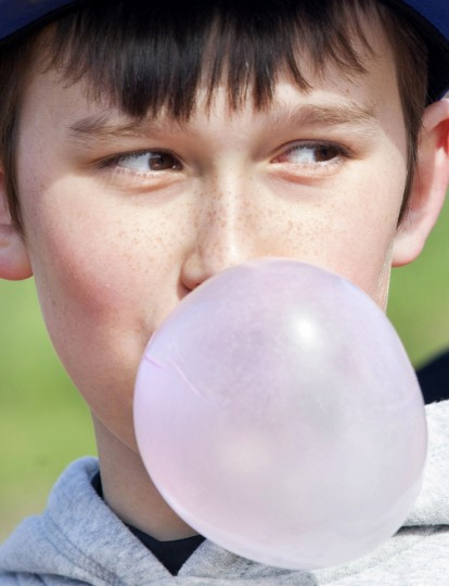 Kameron Moore, 9, blows a professional-sized bubble Saturday, March 28, 2015, while hitting the field for the first day of the Paducah Dodgers 10-year-old recreation league baseball team at Noble Park in Paducah. (AP Photo/The Paducah Sun, John Paul Henry)