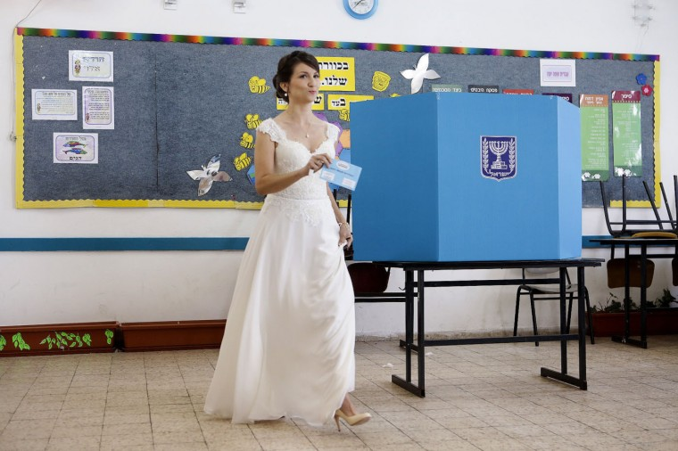 An Israeli bride prepares to cast her vote at a polling station in Holon, Israel, Tuesday, March 17, 2015. Israelis are voting in early parliament elections following a campaign focused on economic issues such as the high cost of living, rather than fears of a nuclear Iran or the Israeli-Arab conflict. (AP Photo)