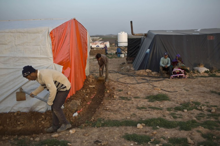 In this Sunday, March 8, 2015 photo, Syrian refugee men dig a ditch around their tent at an Informal Tented Settlement near the Syrian border, on the outskirts of Mafraq, Jordan. Some refugees say they pitched tents to be close to jobs on farms, especially during harvest season. Others say they can't afford rent or that they don't want to live in the authorized camps because of restrictions there. (AP Photo/Muhammed Muheisen)