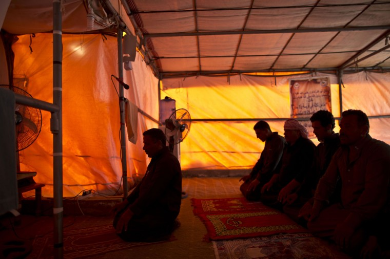 In this Sunday, March 8, 2015 photo, Syrian refugees pray in a makeshift mosque inside a tent at an informal tented settlement on the outskirts of Mafraq, Jordan. (AP Photo/Muhammed Muheisen)
