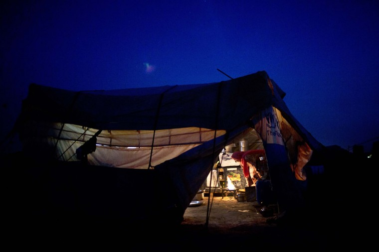In this Sunday, March 8, 2015 photo, a Syrian refugee woman cooks inside her tent at an informal tented settlement near the Syrian border, on the outskirts of Mafraq, Jordan. (AP Photo/Muhammed Muheisen)
