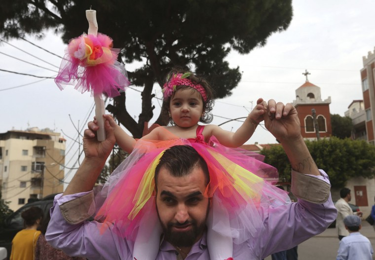An Assyrian man carries his daughter on his shoulders as she holds a candle in front of the Assyrian church, background, during the traditional Palm Sunday procession, east of Beirut, Lebanon, Sunday, March 29, 2015. In late February, the Islamic State group took captive more than 220 Christians from villages in Syria's northeastern province of Hassakeh. Some 19 have been freed. Since that incident, scores of Assyrian Christians from Hassakeh have fled to safety in neighboring Lebanon, that has the largest percentage of Christians in the Middle East. Streams of Christian pilgrims gathered Sunday to celebrate the path of Jesus Christ's last journey into Jerusalem, when his followers laid palm branches in his path, before his crucifixion. Streams of Christian pilgrims gathered Sunday to celebrate the path of Jesus Christ's last journey into Jerusalem, when his followers laid palm branches in his path, before his crucifixion. (AP Photo/Hussein Malla)