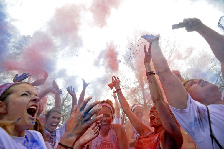 Participants throw color powder in the air after a Color My Campus 5k Color Run in Oxford, Miss., Saturday, March 21, 2015. (AP Photo/The Daily Mississippian, Thomas Graning)