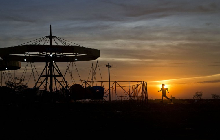 A boy runs to the fair as the sun sets in El Crucero, Nicaragua, Sunday, March 30, 2015. The town holds a fair once a year to celebrate its founding. (AP Photo/Esteban Felix)