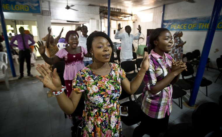 Members of the congregation raise their hands in celebration and prayer during a sermon at the Banner of Life bible church in the mainly Christian Sabon Gari neighborhood of Kano, northern Nigeria on Palm Sunday, March 29, 2015. Many churches in the area were only half-full on Sunday, due to large numbers of Christians leaving before the elections, fearing violence and retribution after election results will be announced in the predominantly Muslim town. (AP Photo/Ben Curtis)