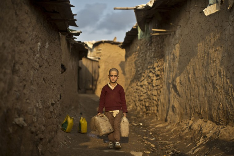 An Afghan refugee boy walks toward a hand pump to fetch water, in a slum on the outskirts of Islamabad, Pakistan, Tuesday, Feb. 3, 2015. (AP Photo/Muhammed Muheisen)