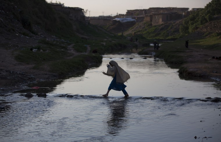 A Pakistani displaced girl, who fled from a Pakistani tribal area where security forces are fighting against militants, crosses a stream in suburbs of Islamabad, Pakistan, Friday, March 20, 2015. (AP Photo/B.K. Bangash)