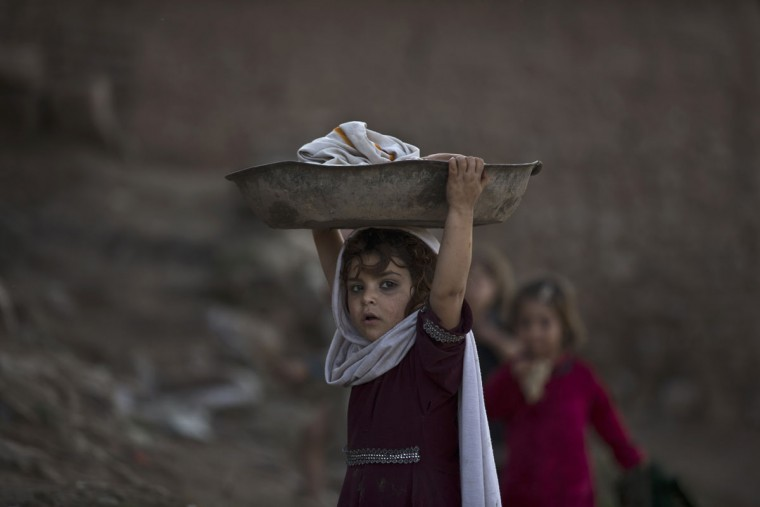 An Afghan refugee girl carries laundry on her head on the outskirts of Islamabad, Pakistan, Sunday, Feb. 22, 2015. (AP Photo/Muhammed Muheisen)