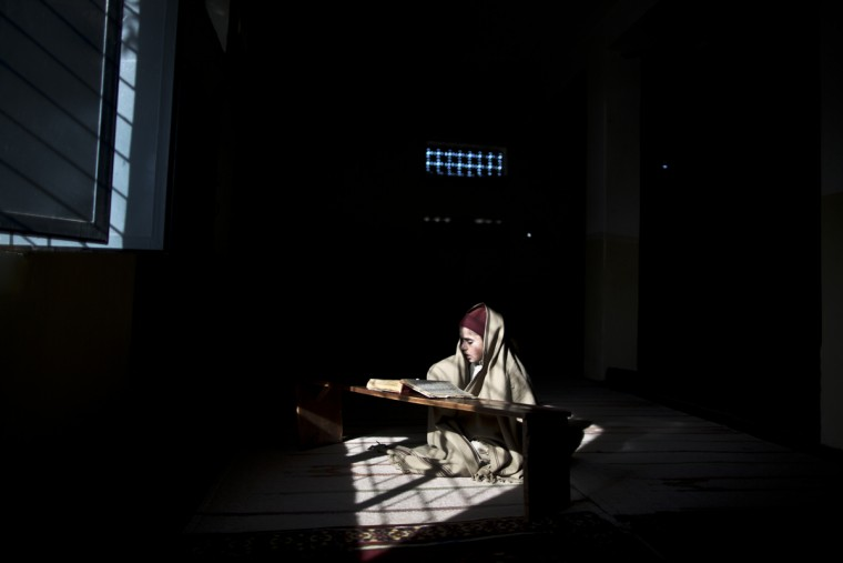 In this Thursday, Feb. 5, 2015, photo, a Pakistani student of a madrassa, or Islamic school, sits on a spot of light as he is wrapped in a shawl to warm himself while reading verses of the Quran prior to a class at a seminary in Islamabad, Pakistan. Thereís no exact number of madrassas in Pakistan but estimates put the number in the tens of thousands. They provide food, housing and a religious education to students from around the country. (AP Photo/Muhammed Muheisen)