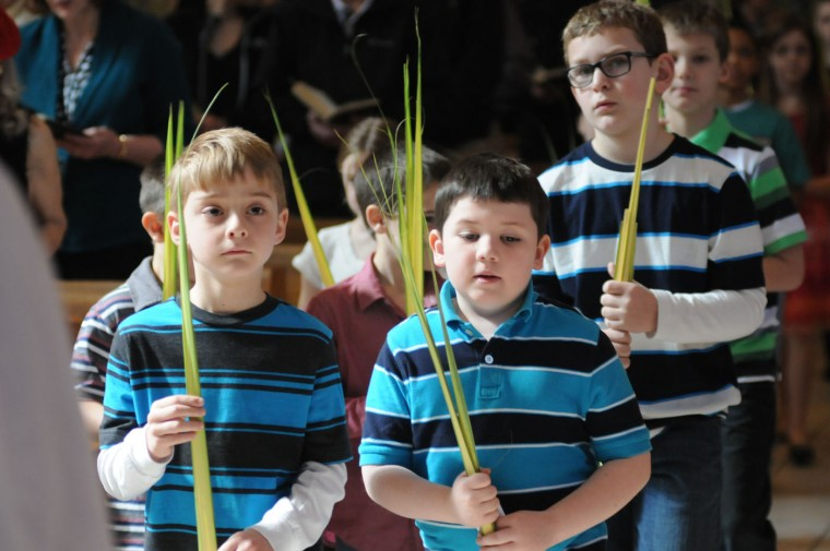 About 25 St. Patrick's Church parish children proceed into the church carrying palms during the Palm Sunday service at the church in Pottsville, Pa., on Sunday, March 29, 2015. From left are, Quinn Evans, 7, Norwegian Township, Ryan Devine, 7, Pottsville, Pa., and Joseph Rossi, 9, of Pottsville, Pa. The children are from the Saint Patrick's Religious Education Program and the Assumption BVM school. (AP Photo/The Republican-Herald, Andy Matsko)