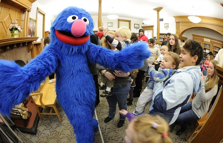 Sesame Strret character Grover reaches out to hug children after a vist to the Osterhout Library, in Wilkes-Barre, Pa., Thursday, March 5, 2015. The Sesame Street characters were in the area for performances at the Mohegan Sun Arena and payed a visit to the library for a children's show. (AP Photo/The Citizens' Voice, Mark Moran)