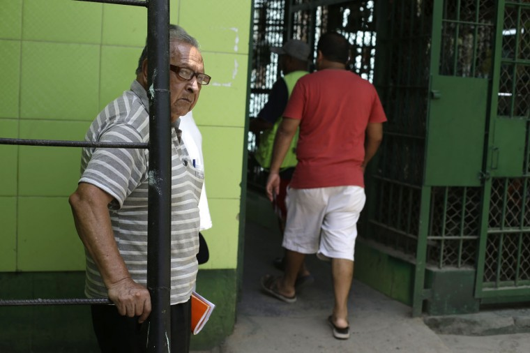 """In this Feb. 27, 2015 photo, 78-year-old Roberto Osoria stands inside the Lurigancho Prison in Lima, Peru. Osoria has spent five years behind bars for a rape conviction with 13 years remaining in his sentence. Osoria refuses to talk about the crime and complains he has to sleep on the floor and eat bad food. """"I'm going blind,"""" he said, crying. (AP Photo/Martin Mejia)"""