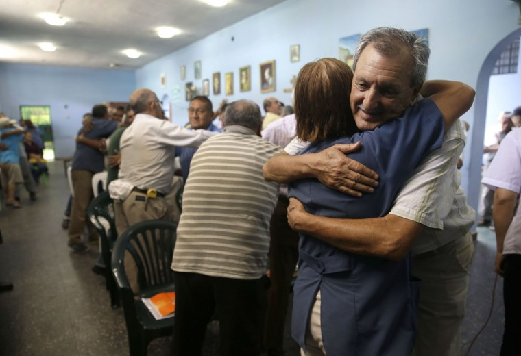 In this Feb. 27, 2015 photo, inmate Rolando Velasco, 70, who is serving time for drug trafficking, embraces the prison psychologist during a group therapy session at the Lurigancho men's prison in Lima, Peru. The prison system offers dozens of art-based workshops and therapeutic sessions for the elderly prisoners. (AP Photo/Martin Mejia)
