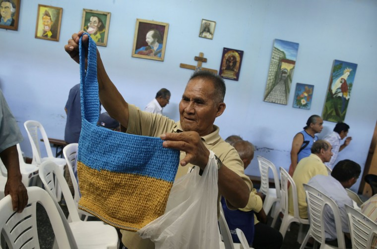 In this Feb. 27, 2015 photo, Alfonso Cruz, 76, holds up a woman's bag he crocheted, at the Lurigancho men's prison in Lima, Peru. Cruz, who learned to crochet in one of the workshops offered at the prison, hands off the bags to his family during visits, to sell for him. (AP Photo/Martin Mejia)