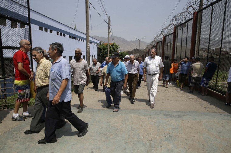 In this Feb. 27, 2015 photo, elderly inmates take a 30-minute walk around the perimeter of the prison as part of their exercise at the Lurigancho men's prison in Lima, Peru. Reportedly 2,500 inmates over 60 are incarcerated in the South American country's prisons. (AP Photo/Martin Mejia)