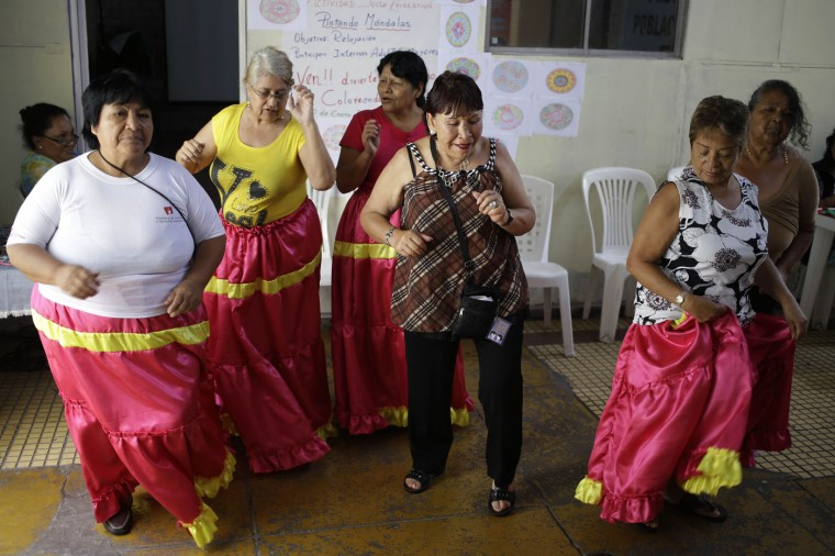 """In this Jan. 30, 2015 photo, prisoner Luz Ludena, 63, center, takes part in a dance class with fellow inmates inside the Santa Monica women's prison in Lima, Peru. A mother of three, Ludena is serving a second prison term for drug-trafficking. """"My heart is as young as an 18-year-old, I still have desire to love and be loved,"""" she said. (AP Photo/Martin Mejia)"""
