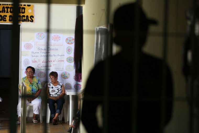 """In this Jan. 30, 2015 photo, two female inmates chat, backdropped by mandala drawings at the Santa Monica women's prison in Lima, Peru. There are dozens of workshops in Peruís prisons, which hold more than 70,000 inmates. Prisoners pass the time in different fashions. Some read from the Bible, some take dance or art classes while others just simply """"survive."""" (AP Photo/Martin Mejia)"""